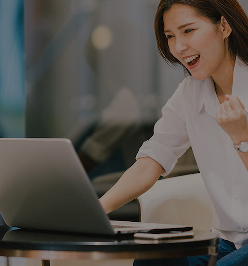 woman happily studying on computer